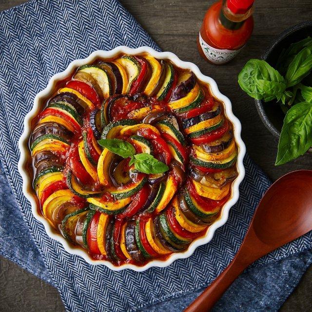 カラフル野菜をたっぷり使ったラタトゥイユに、素材の味をしっかり引き出すTABASCO®ソースをプラスすれば一気に本格的なフランス料理の味わいに。#タバスコ #世界をちょっピリおいしく  材料: ナス 1本 ズッキーニ、緑と黄  各1本 トマト(中玉)3個 バジル (飾り用)数枚  〈トマトソース〉 トマト缶 (ダイス状)1缶 にんにく(みじん切り)1カケ バジル 1つまみ 塩コショウ  1つまみ ケチャップ 大さじ1 白ワイン 大さじ1 TABASCO®ソース 大さじ2  ・ナス、ズッキーニ、トマトをそれぞれ2〜5ミリの幅で輪切りにし、塩コショウ を軽くふっておく。 ・〈トマトソース〉をつくる。 小鍋かフライパンにオリーブオイルをしき、にんにくが香ったところに調味料を全て入れ、軽く煮詰める。 ・耐熱皿にトマトソースをしき、その上に切った野菜を彩りよく交互に敷き詰めてからオリーブオイルをまわしかけ、塩コショウを全体に軽くふる。 ・180度のオーブンで15〜20分程度グリルし、仕上げにバジルの葉を散らしたら完成。 ※再度お好みでTABASCO®ソースをふりかける。 . . . . . #ラタトゥイユ #フランス料理 #おつまみ #野菜料理 #ビール #家飲み #飲み会 #おうちごはん #おうちバー
